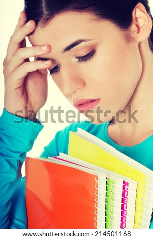 Portrait of young sad female student with workbook. Isolated on white. - stock photo