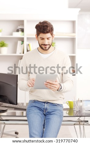 Portrait of young sales man standing at office in front of desk and holding in his hand digital tablet. Businessman touching the screen while writing email on touchpad.  - stock photo