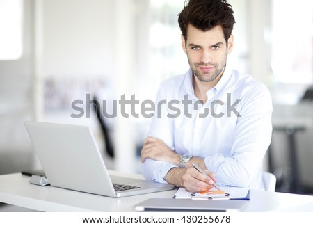 Portrait of young sales man working on laptop while sitting at his workplace.
