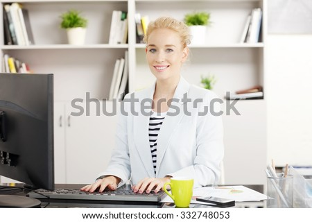 Portrait of young sales woman sitting at office and working online. Smiling professional typing on keyboard while writing business presentation.