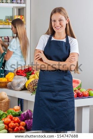 Portrait of young saleswoman standing arms crossed with woman shopping in background - stock photo