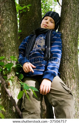 portrait of young schoolboy in a cap and scarf, sitting on a tree - stock photo