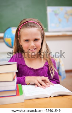 Portrait of young schoolgirl reading a book in a classroom