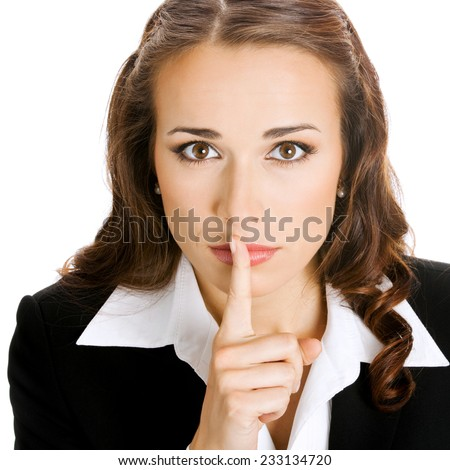 Portrait of young serious business woman keeping finger on her lips and asking to keep quiet, isolated against white background - stock photo