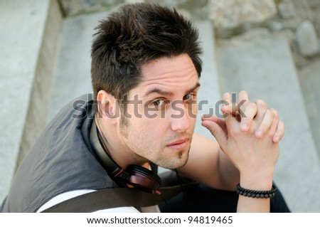 Portrait of young serious man sitting on steps, with headphones - stock photo