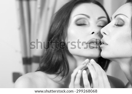 Portrait of young sexual attractive brunette woman with bright makeup and open mouth touching and reflecting in mirror sitting with closed eyes black and white, horizontal picture - stock photo