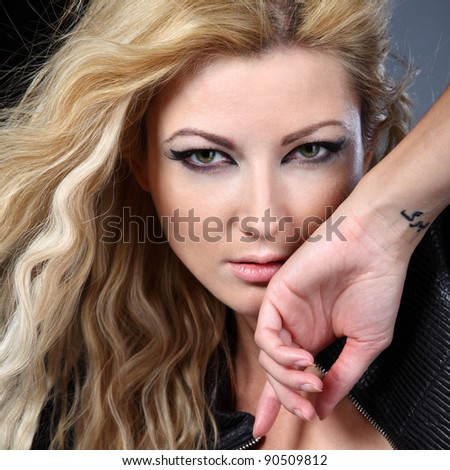 portrait of young sexual woman with tattoo on the carpus - stock photo