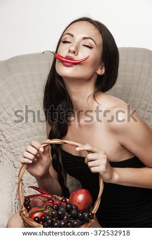 Portrait of young sexy brunette sitting in armchair and eating  hot chili pepper. Beautiful woman dressed in black posing in studio.  - stock photo