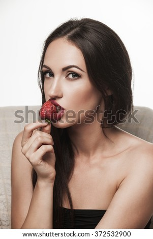 Portrait of young sexy brunette sitting in armchair and eating  strawberry. Beautiful woman dressed in black posing in studio.  - stock photo