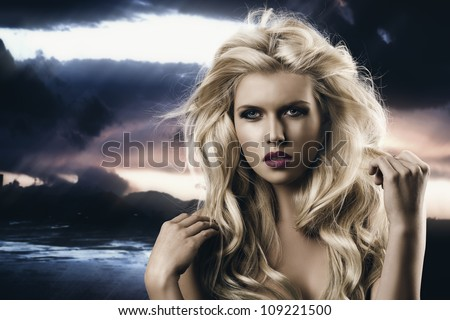 portrait of young sexy girl with blode wavy hairstyle and and flying hair from wind, she is in front of the camera and looks in to the lens, her right hand is near the right shoulder - stock photo