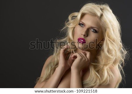 portrait of young sexy girl with blode wavy hairstyle and and flying hair from wind, she is turned of three quarters at right and her both hands are near the face - stock photo