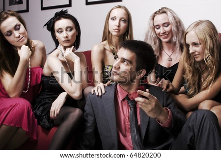 Portrait of young sexy lovelace man surrounded by hot women wanting of proposal from him