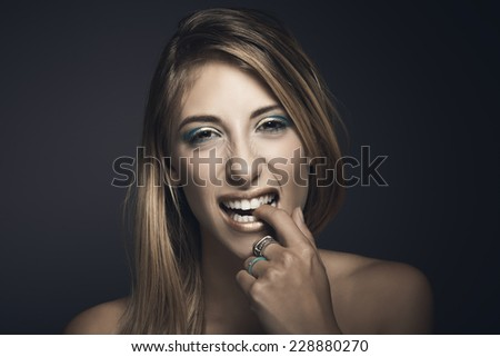 Portrait of young sexy woman biting her fingers against blue background - stock photo