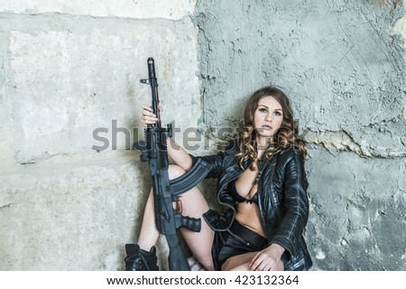 portrait of young sexy woman in a leather jacket and sexual brassiere with a Kalashnikov in her hand. Girl stand against brutal concrete wall - stock photo