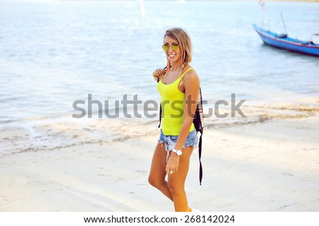 Portrait of young sexy woman in jeans shorts with bag having fun and walking on a beach  - stock photo