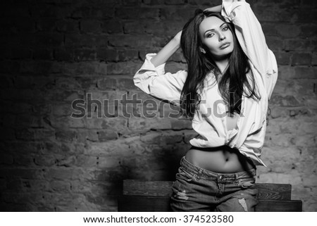 Portrait of young sexy woman posing in shirt and jeans. Monochrome - stock photo