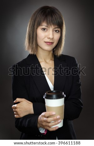 portrait of young sharply dressed business woman holding a take away cup shot in the studio low key lighting on a gray background - stock photo
