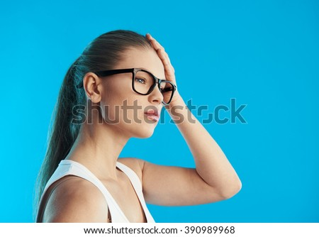 Portrait of young sick female suffering from migraine or vertigo over blue background. Concept of head illness diagnosis and treatment. - stock photo