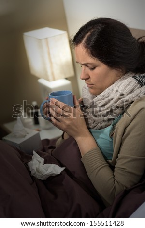 Portrait of young sick woman drinking tea suffering from cold - stock photo