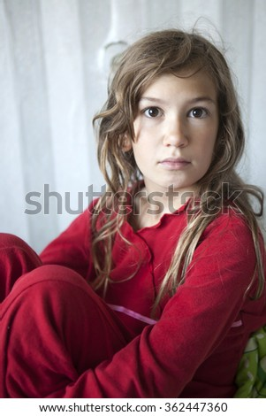 portrait of young sleepy girl eleven years old in red pyjamas sitting on the bed - stock photo