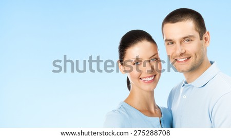 Portrait of young smiling amorous attractive couple, over blue sky background, with blank copyspace area for text or slogan - stock photo