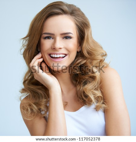 Portrait of young smiling beautiful woman on natural background - stock photo