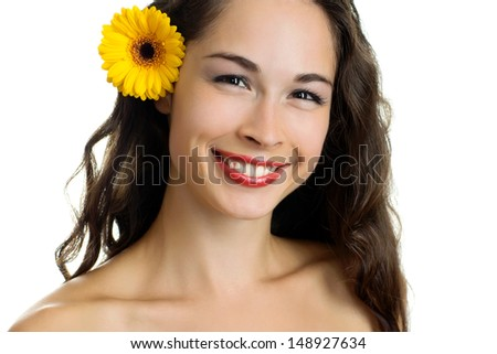 Portrait of young smiling beautiful woman with a gerbera on white background