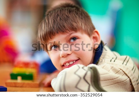 portrait of young smiling boy, kid with disabilities - stock photo