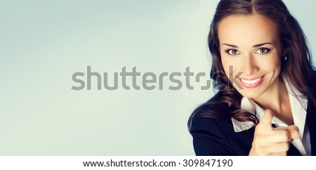 Portrait of young smiling brunette businesswoman pointing finger at viewer, with blank copyspace area for slogan or text message