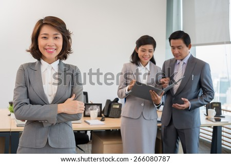 Portrait of young smiling business lady and her colleagues talking in the background