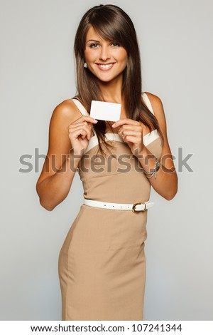 Portrait of young smiling business woman holding credit card isolated on gray background - stock photo