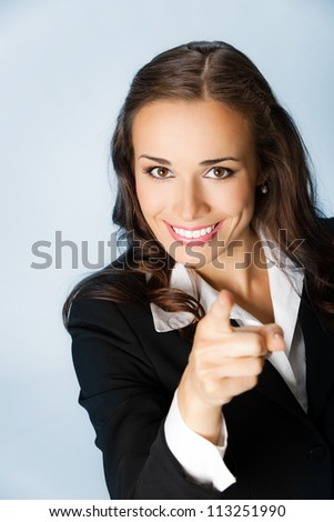 Portrait of young smiling business woman pointing finger at viewer, over blue background - stock photo