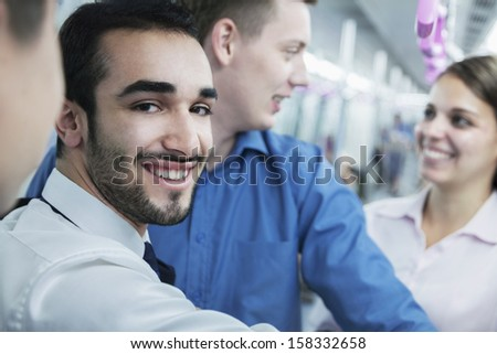 Portrait of young smiling businessman standing on subway - stock photo