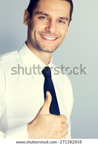 Portrait of young smiling businessman with thumbs up gesture, specially toned - stock photo