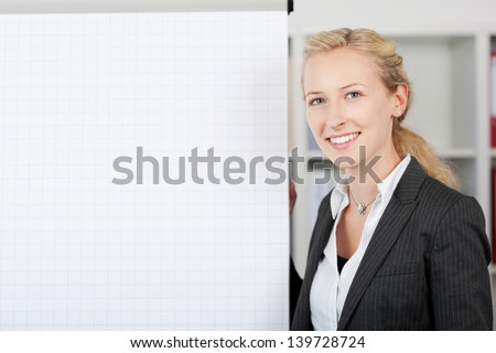 Portrait of young smiling businesswoman standing by flipchart in office - stock photo