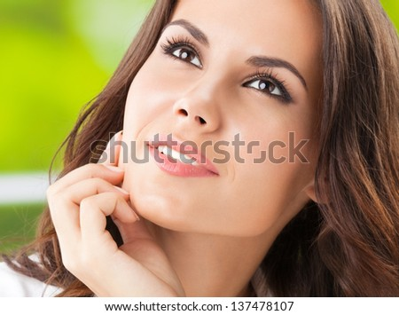 Portrait of young smiling cheerful thinking woman
