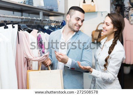 Portrait of young smiling couple choosing new apparel in store