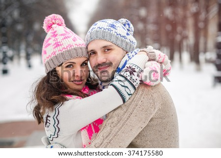 Portrait of young smiling couple in scarf and sweaters in winter city park