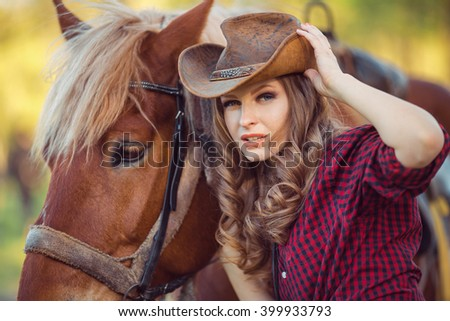 Portrait of young smiling cowgirl and horse outdoors