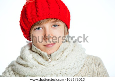 Portrait of young smiling cute teenager in a red hat and mittens, isolated on white