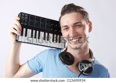 Portrait of young smiling deejay with headphones and midi keyboard on his shoulder.Piercing near mouth. - stock photo