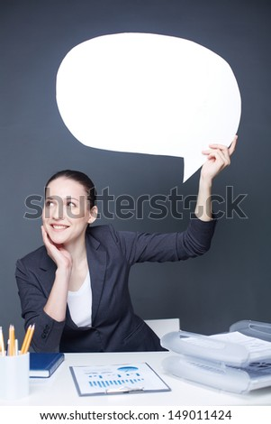 Portrait of young smiling female holding paper speech bubble - stock photo