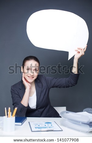 Portrait of young smiling female holding paper speech bubble and looking at camera - stock photo