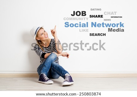 Portrait of young smiling girl sitting on the floor in empty room, pointing on social network chart. Concept of internet communication and technology.  - stock photo