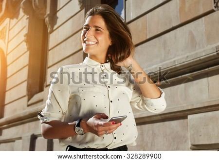 Portrait of young smiling girl using mobile phone while stroll in sunny day outdoors, happy female model chatting on her smart phone while walking in the city,  stylish women using technology - stock photo