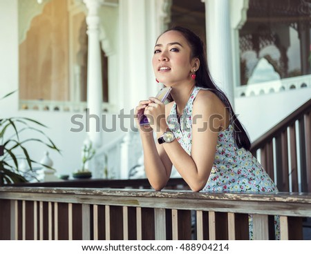 Portrait of young smiling girl using mobile phone while stroll in sunny day outdoors, happy female model chatting on her smart phone
