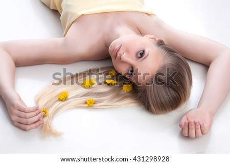 Portrait of young smiling girl with beauty face lying on the floor. Yellow dress. Long blonde hairs with dandelion flowers. - stock photo