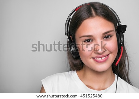 Portrait of young smiling girl with headset looking at camera.Isolated. - stock photo