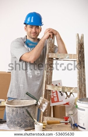 Portrait of young smiling guy surrounded with painting equipment.