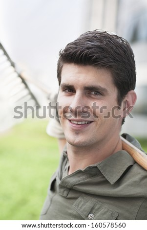Portrait of young smiling man holding rake on roof top garden in the city - stock photo